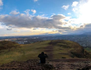 man taking photo on arthurs seat edinburgh penguin and pia