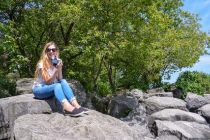 blonde girl with camera sitting in rocks by the lake penguin and pia travel