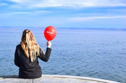 blonde hair girl sitting with red balloon penguin and pia sherpa