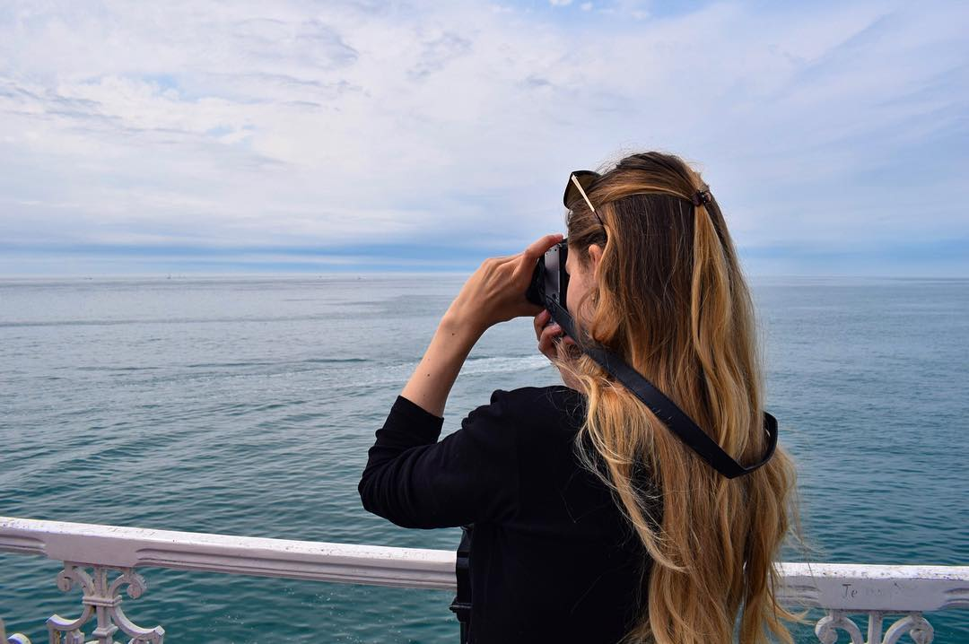 Girl taking photo with ocean in background