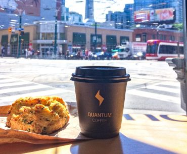 coffee cup on wooden counter with scone best coffee shops in toronto