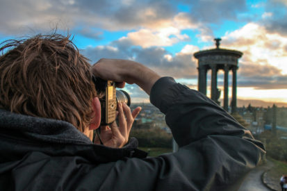 boy with camera taking photo of monument on calton hill edinburgh penguin and pia