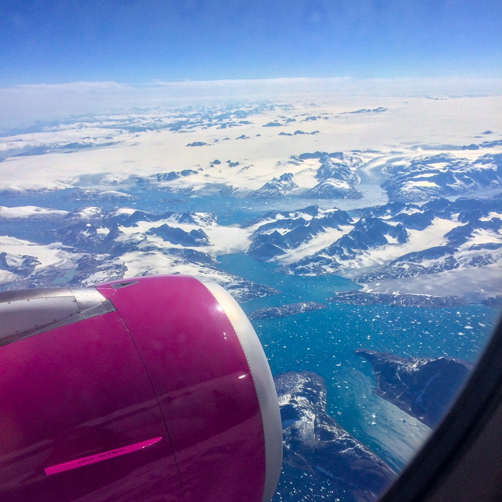 pink plane engine over blue landscape from airplane booking cheap flights