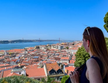 girl looks over lisbon roofs with bridge and water penguin and pia travel lisbon stopover