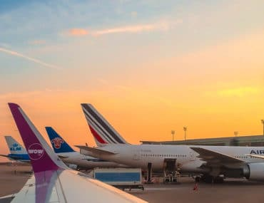 booking europe stopover flight airplane wings with sunset