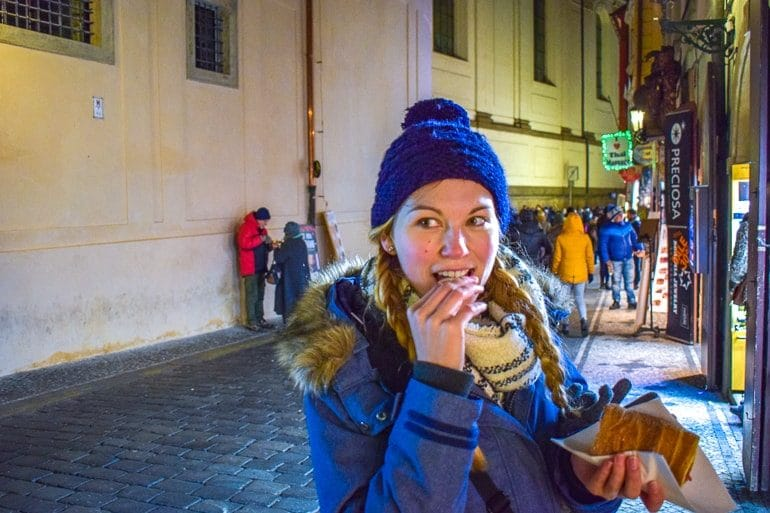 girl in blue coat with hat eating dessert things to do in prague