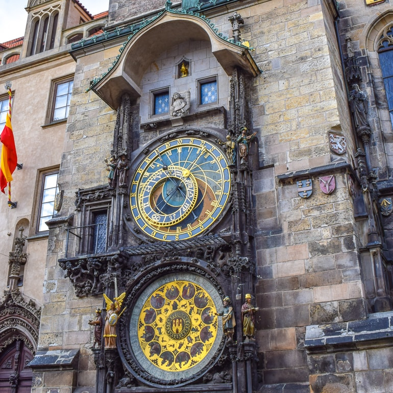gold and stone clock on wall things to do in prague