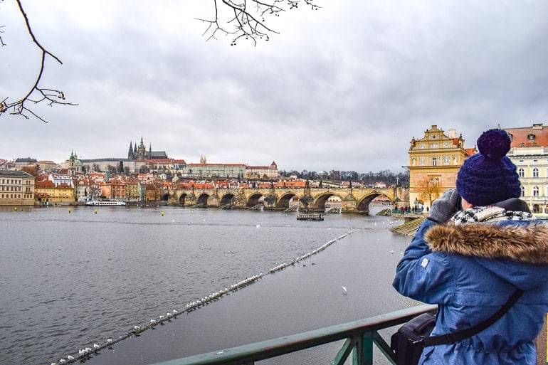 long bridge over river with girl taking photo things to do in prague