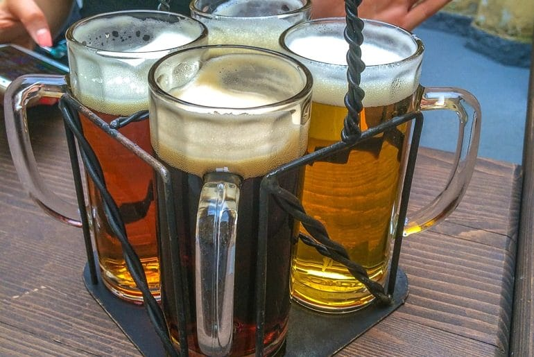 four beer in mugs on wooden table things to do in prague