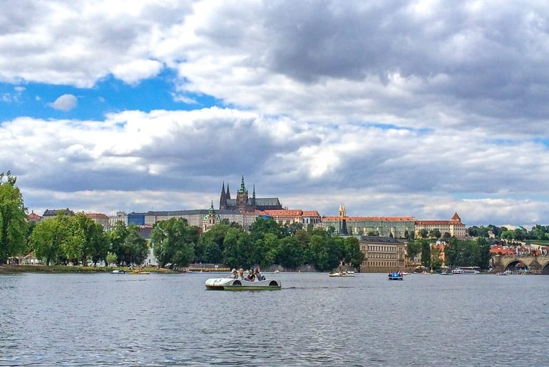 people in paddle boat on river with prague castle behind things to do in prague