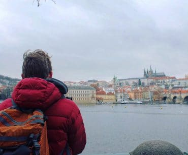 man with orange backpack looking over water and prague castle