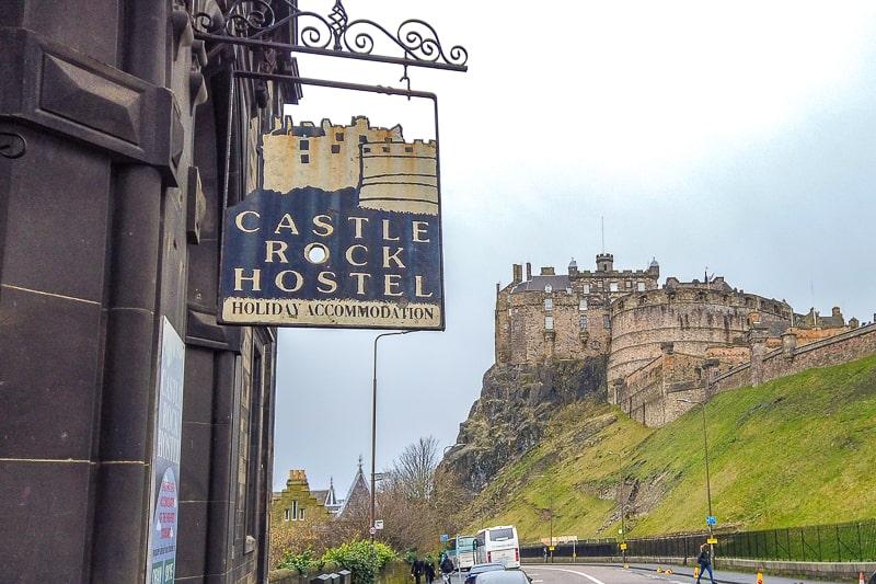 Hostelschild hängt im Vordergrund mit Schloss von Edinburgh dahinter