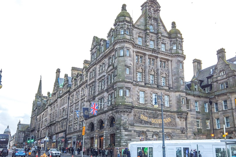 altes Hotelgebäude mit Flaggen davor entlang geschäftiger Straße