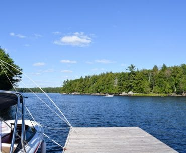 boat and wooden dock lookng over blue lake and green trees of ontario cottage rental