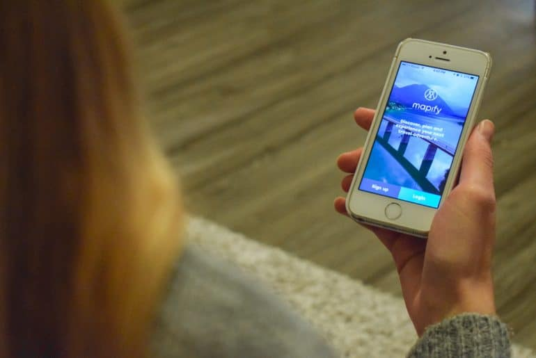 smartphone with travel apps open in hand