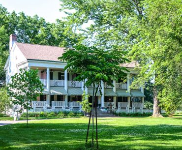 old white house with veranda through green trees ontarios finest inns