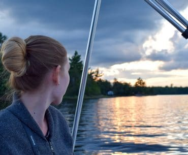girl sitting in boat looking at blue lake with sunset