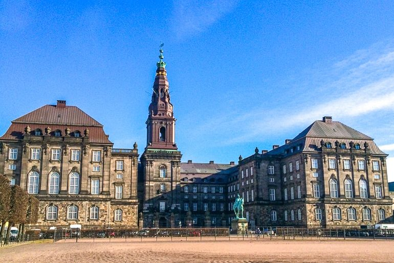 large brown palace with tower and dirt field in front christiansborg palace denmark