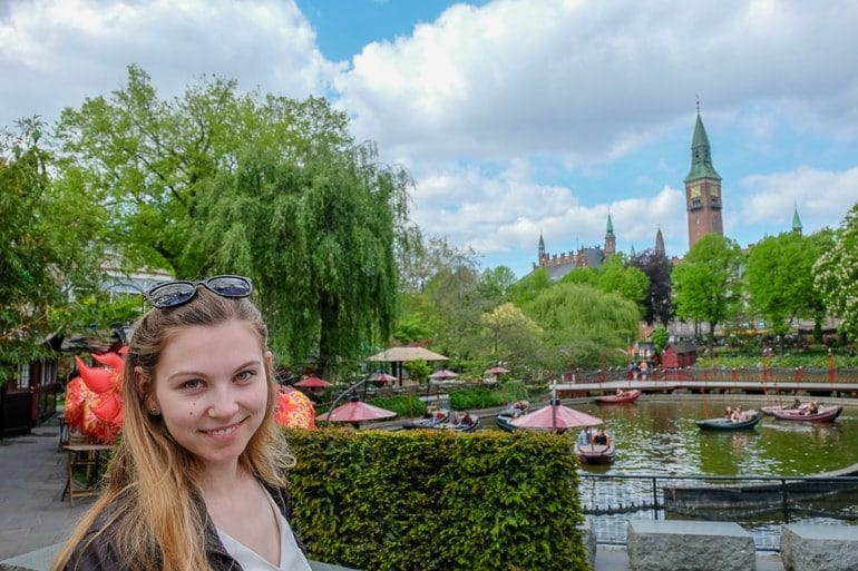 girl in front of lake with trees and tower behind at tivoli gardens