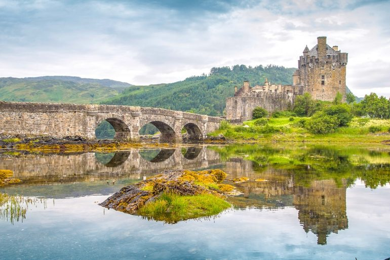 medieval stone castle with bridge and water in front day trips from edinburgh highlands