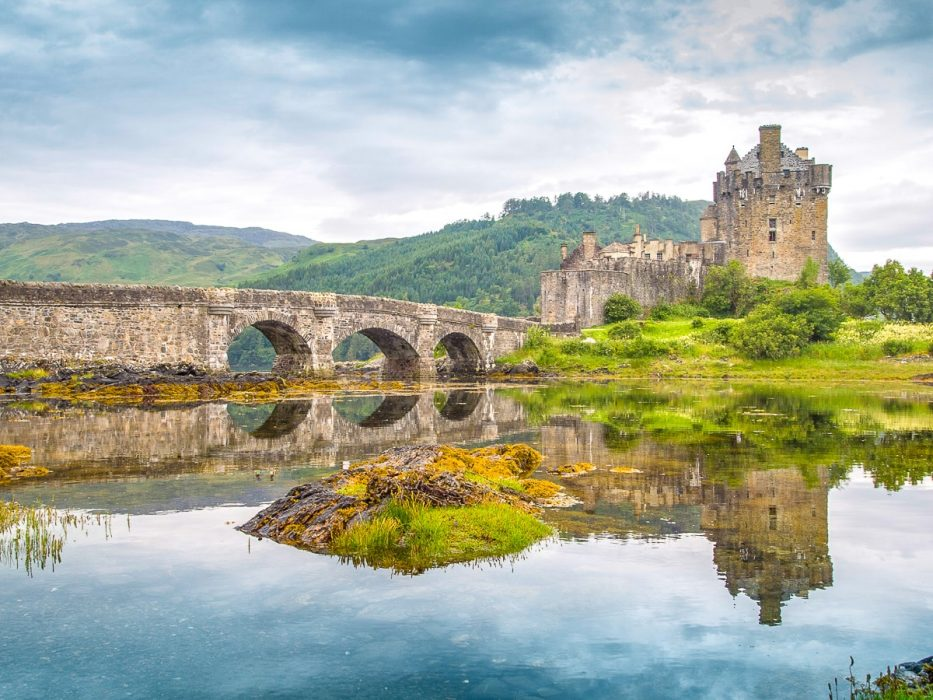 old stone castle with green hills and bridge experiences of a lifetime scottish highlands