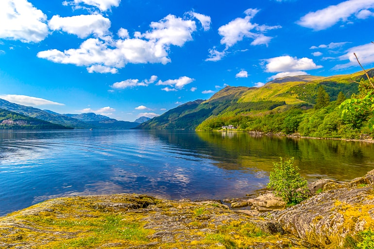 blue lake with green rolling hills beside loch lomond scotland