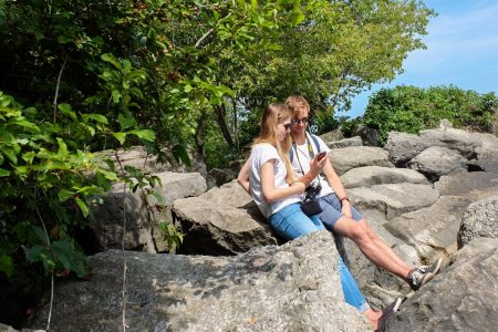 girl and boy sitting on rocks with trees in background