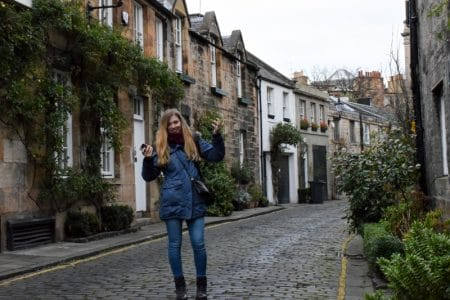 girl standing in edinburgh alleyway with arms raised