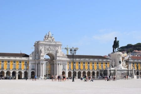open square in lisbon portugal with blue sky and yellow buildings
