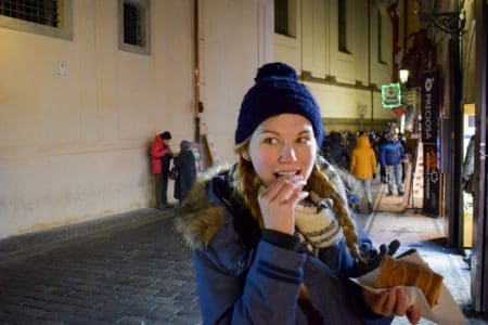 girl eating pastry in alleyway in prague