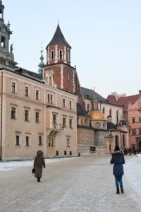 woman and girl walking with wawel castle in background