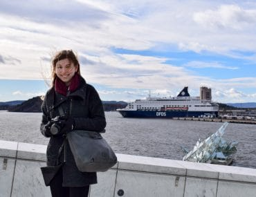 girl in oslo norway with cruise ship and water in background