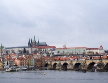 prague castle and buildings along the river with charles bridge