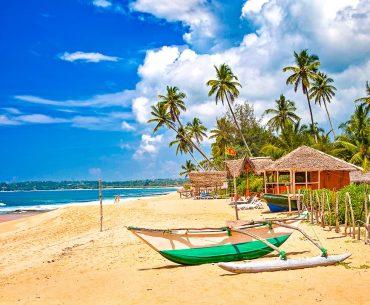 green wooden boat on sandy beach with hut and palm trees sri lanka eta visa