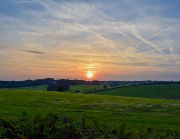 orange sunset over green rolling hills