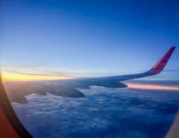 airplane wing with blue clouds and sunrise