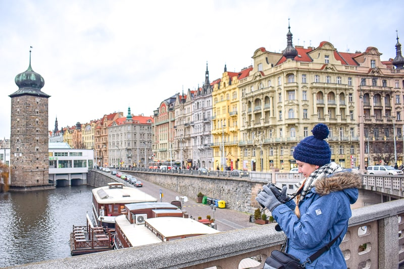 Frau mit Wintermütze steht auf Brücke in Prag mit bunten Gebäuden im Hintergrund