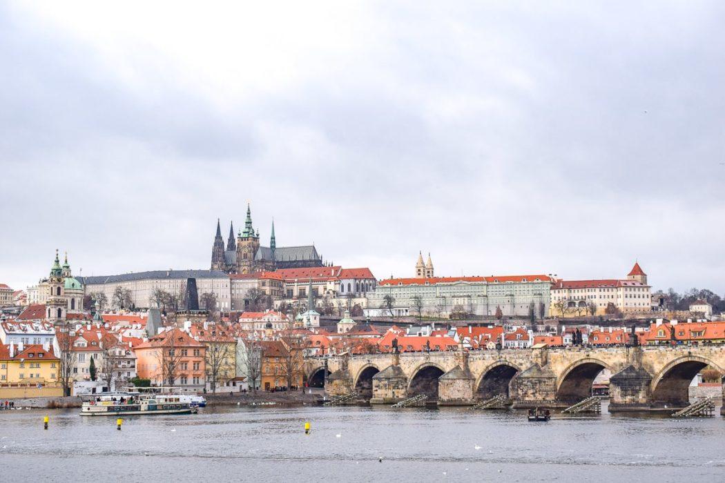 Blick auf Prager Burg auf Hügel mit Karlsbrücke im Vordergrund