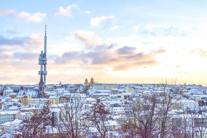 Hoher Fernsehturm in Prag mit schneebedeckten Dächern herum