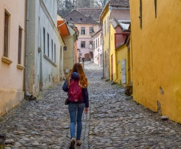 girl with daypack backpack walking though old town