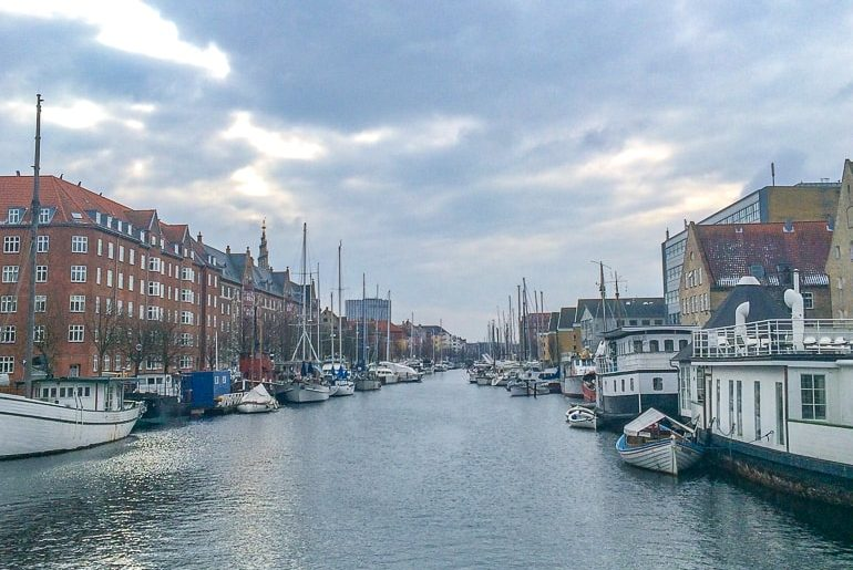 boats along the edge of blue canal with buildings best places to stay in copenhagen
