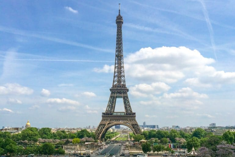 eiffel tower with blue sky and green trees europe trip itinerary
