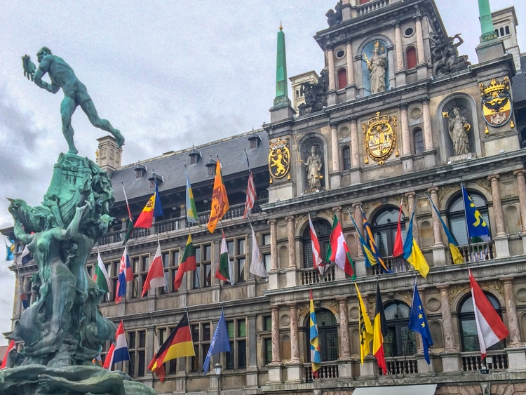 flags on building and statue in antwerp europe trip itinerary