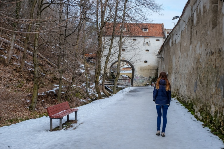 girl walking snowy path with bench and wall beside