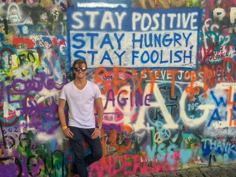 guy standing up against graffiti wall in prague on europe trip itinerary