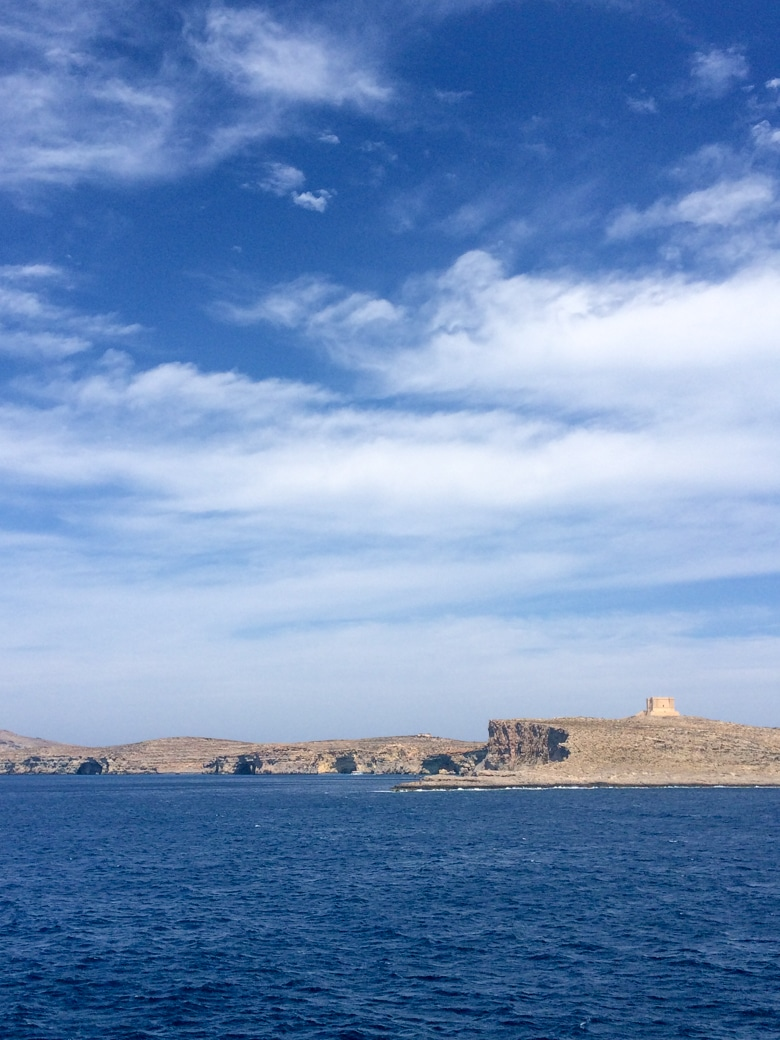 small tower on island of comino with blue sky and water