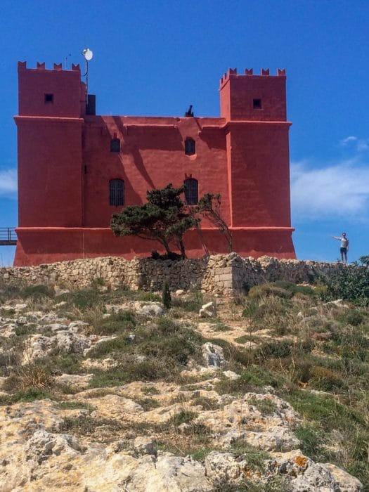 red tower on hilltop with blue sky