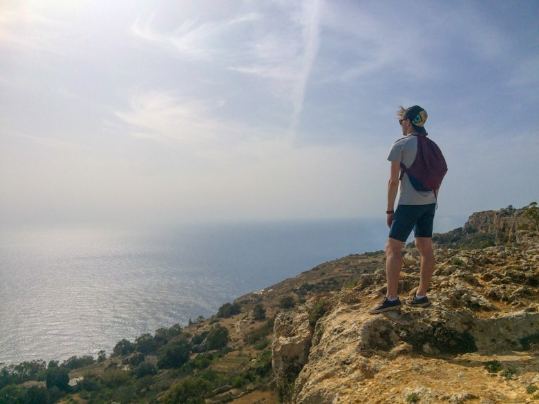 boy with hat standinglooking out over dingli cliffs malta