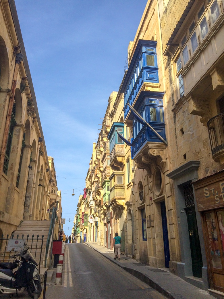 narrow street with blue shutter windows valletta malta