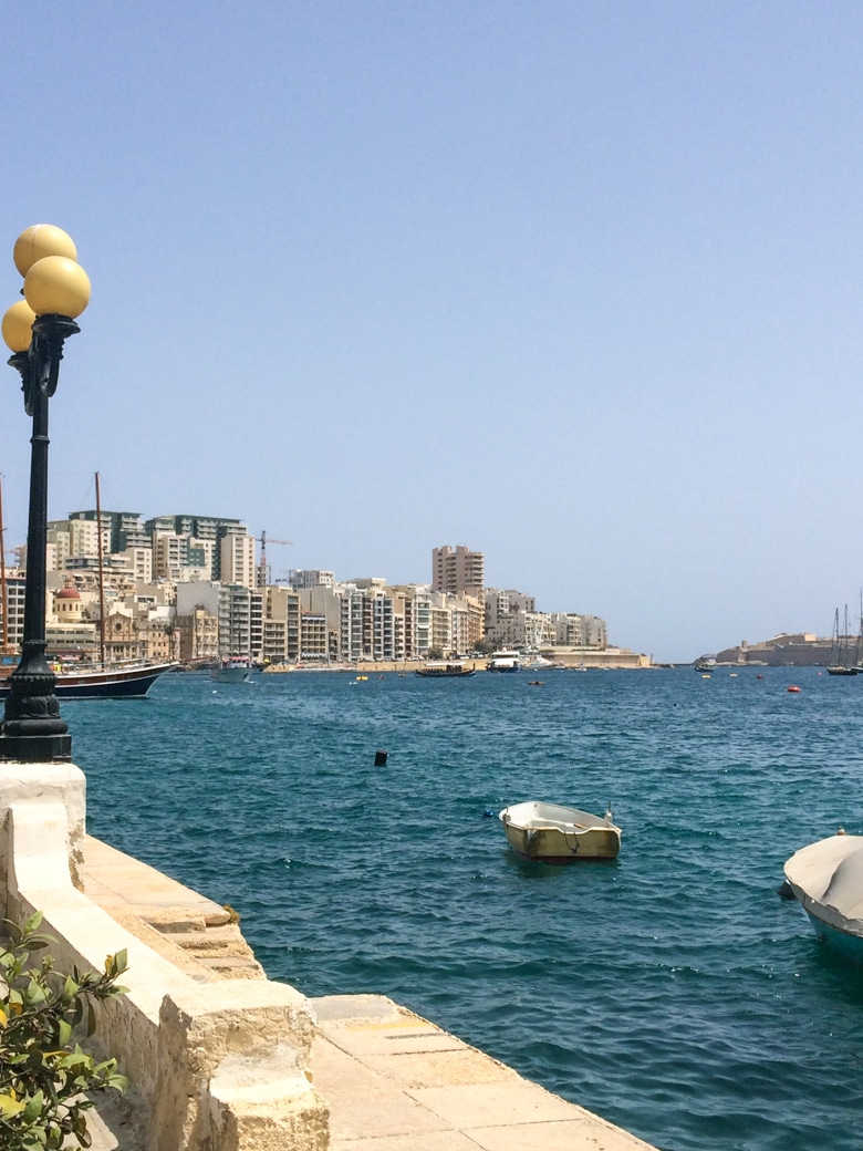 blue water with buildings in sliema malta